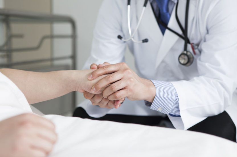 患者の手を両手で握りしめる医者